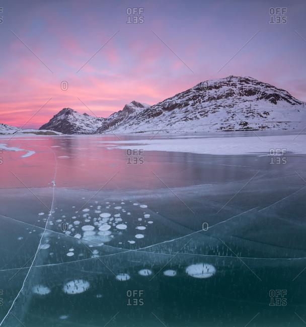Panorama of ice bubbles and frozen surface of Lago Bianco at dawn, Bernina Pass, canton of Graubunden, Engadine, Switzerland, Europe