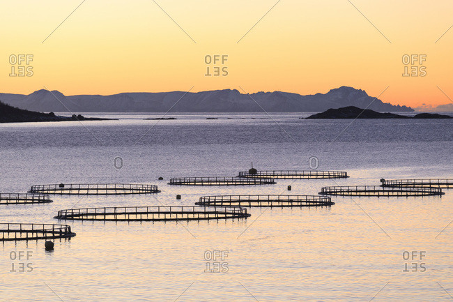 Sunset lights up the fish tanks of codfish and salmon in the cold sea of Torsken, Senja, Troms, Norway, Scandinavia, Europe