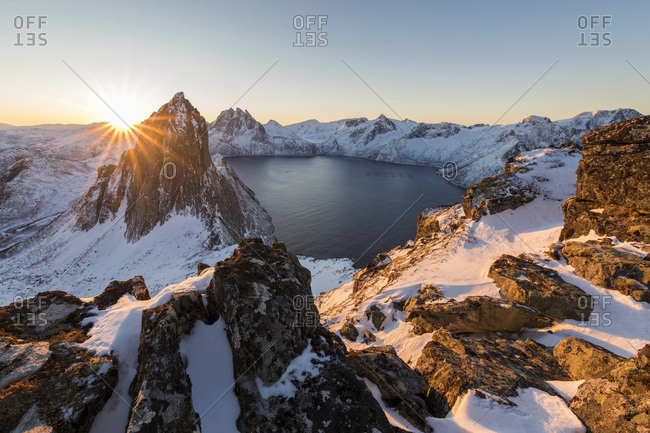 First light of sunrise on Mount Segla and Mefjorden framed by the frozen sea seen from peak Hesten, Senja, Troms, Norway, Scandinavia, Europe
