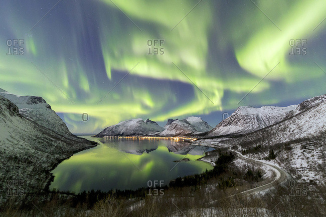 Northern lights (aurora borealis) and stars light up the snowy peaks reflected in the cold sea, Bergsbotn, Senja, Troms, Norway, Scandinavia, Europe