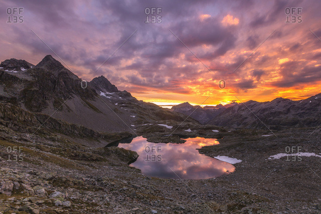 Fiery sky at dawn reflected in Lai Ghiacciato framed by peaks, Val Ursaregls, Chiavenna Valley, Valtellina, Lombardy, Italy, Europe