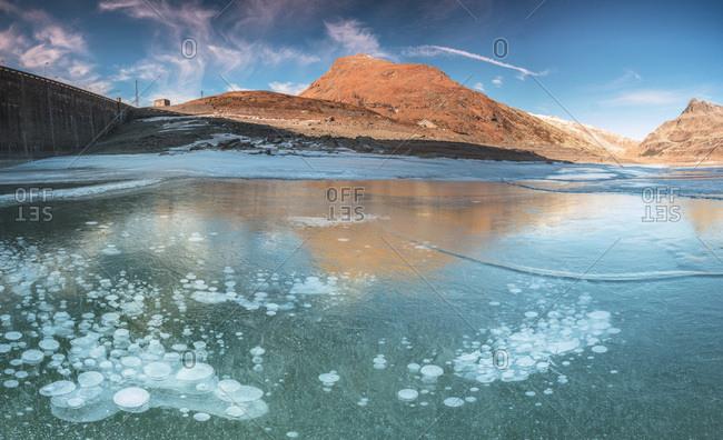 Panoramic of frozen lake Montespluga at dawn, Chiavenna Valley, Sondrio province, Valtellina, Lombardy, Italy, Europe