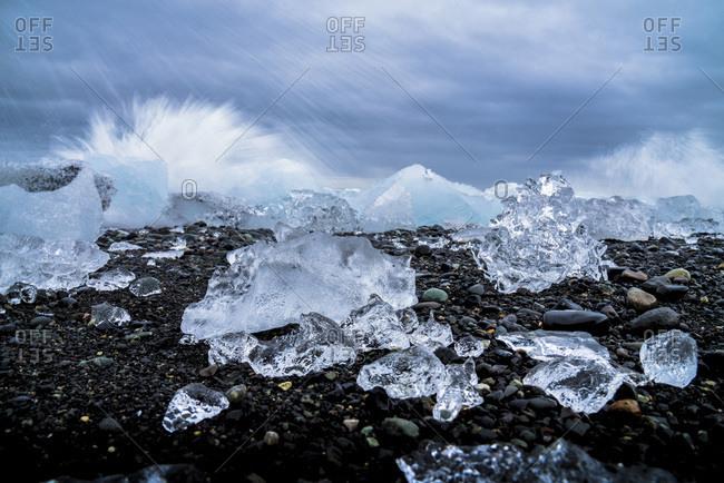 Water crashing over the ice and black sandy beach at Jokulsarlon, Iceland, Polar Regions