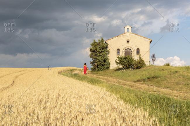 Woman in red dress and wicker basket passing by Notre-Dame-de-Sante chapel, Entrevennes, Alpes-de-Haute-Provence, Provence-Alpes Cote d'Azur, France, Europe
