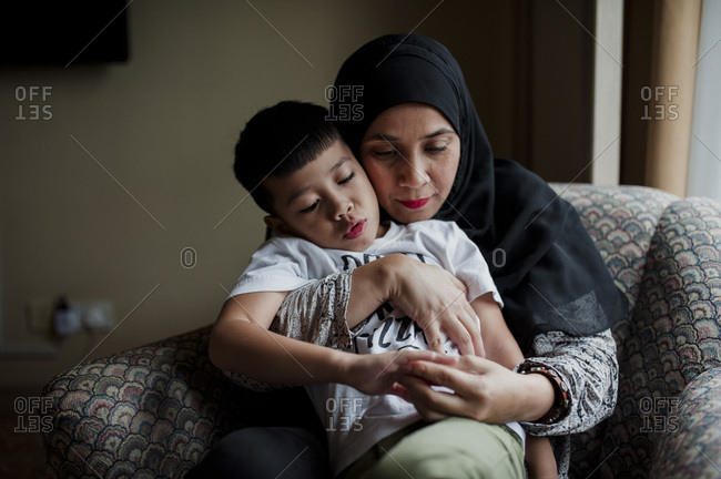 Boy sitting on his mother's lap at home
