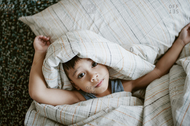 Little boy playing in the bed covers