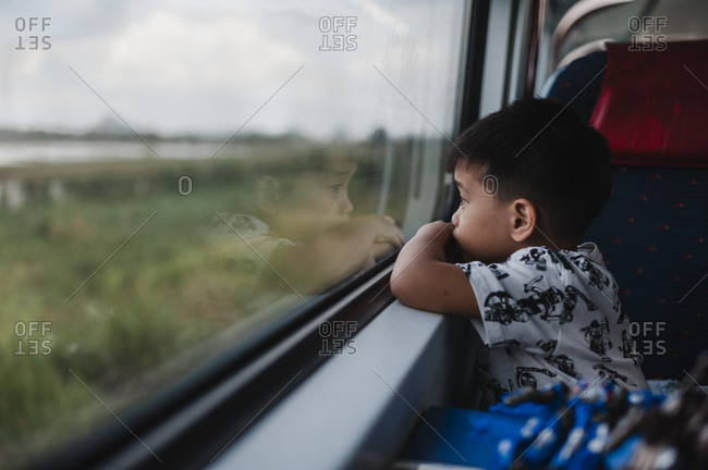 Little boy looking at the scenery out of train window