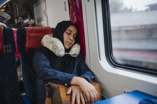 Woman using a travel pillow sleeping on the train