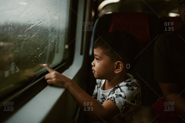Little boy touching window of train on a rainy day
