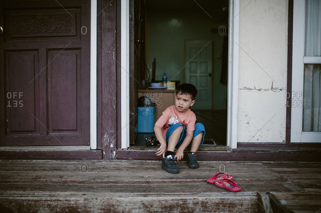 Little boy sitting in doorway putting on his shoes