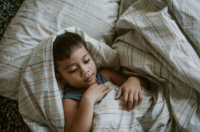 Boy comfortably wrapped in bedsheets