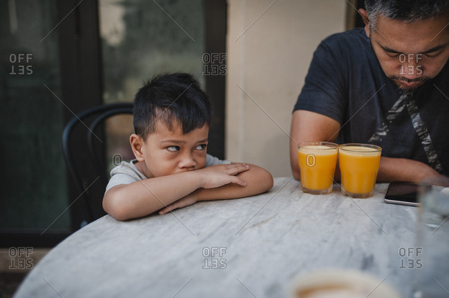 Boy looking up at his dad seated at outdoor table