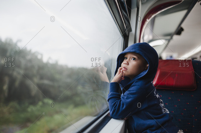 Little boy wearing hooded sweatshirt looking at the scenery out of train window