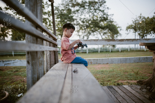 Little boy sitting on bench playing with toy