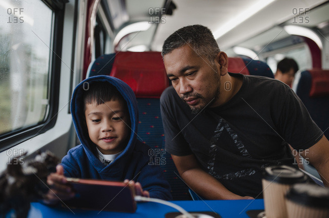 Father and son passing time on train ride looking at phone