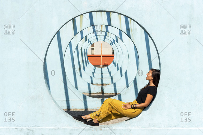 Young woman relaxing in a blue circular structure