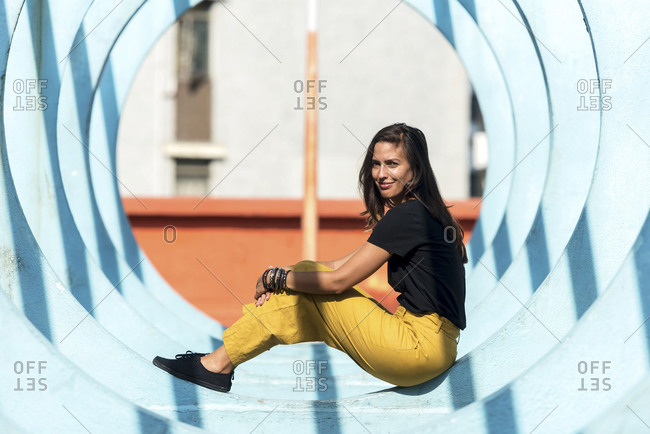 Cool girl sitting in round architectural detail