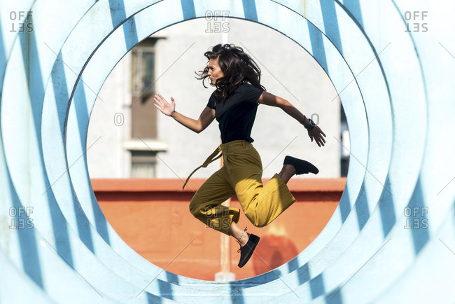 Girl jumping through blue circles spot