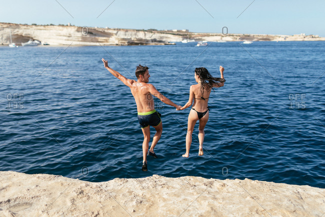 Young couple jump into the sea from the rock, holding hands