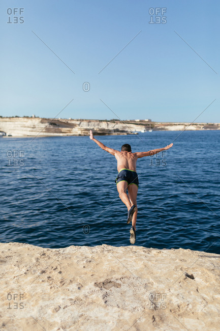 Man jumping from a rock in the sea, summer adventures