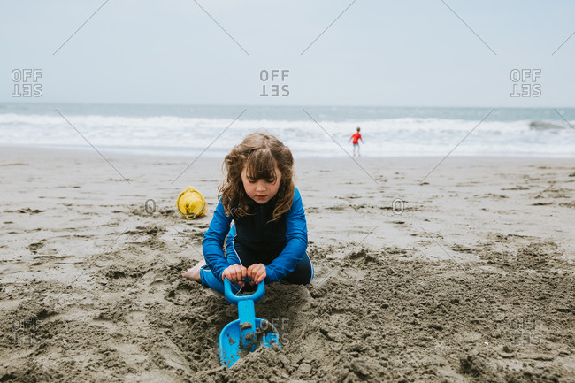 Young girl digging in sand on beach