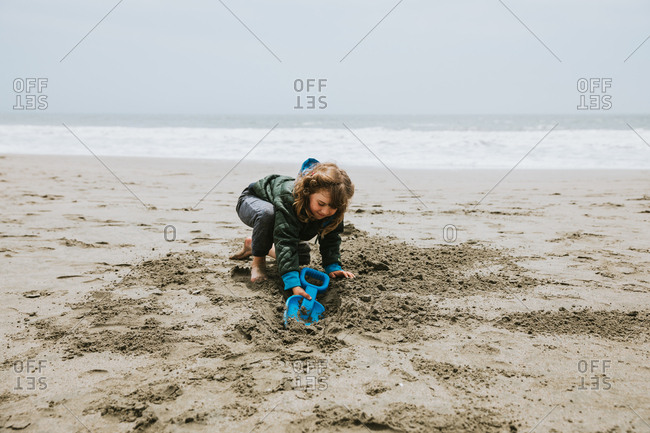 Small girl digging in sand on beach