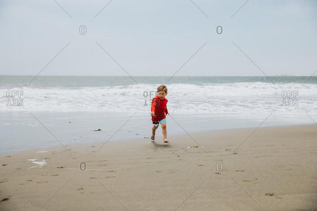 Little boy in running with shovel full of sand on beach