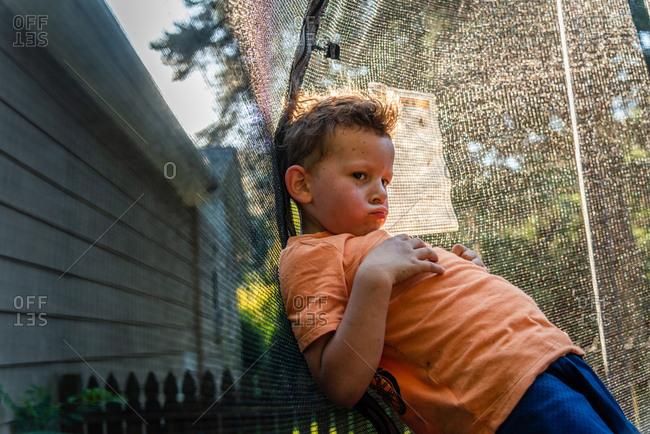 Boy leaning on net on a trampoline