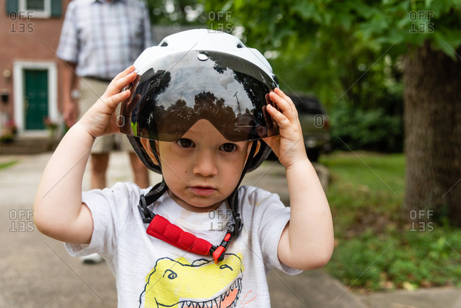 Boy wearing helmet in driveway with grandfather standing behind him