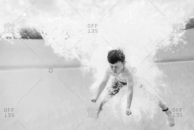 Little boy underwater in pool in black and white
