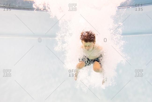 Little boy underwater in pool