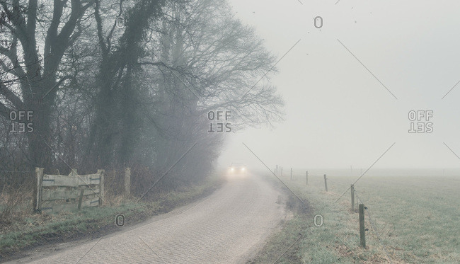 Car driving on foggy country road