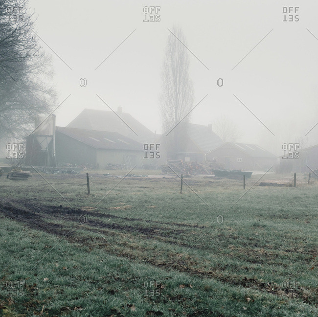 Old farm surrounded by dense fog