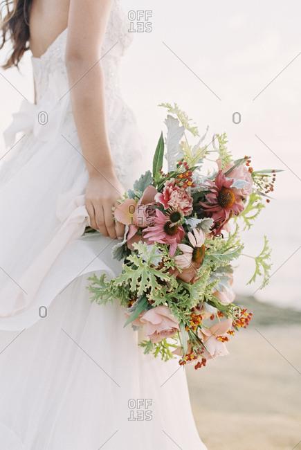 Bride on beach holding bouquet