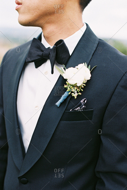 Groom wearing black suit and boutonniere