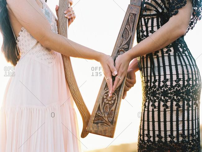Two women holding harp at wedding
