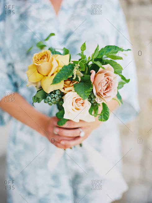 Bride in robe holding bouquet