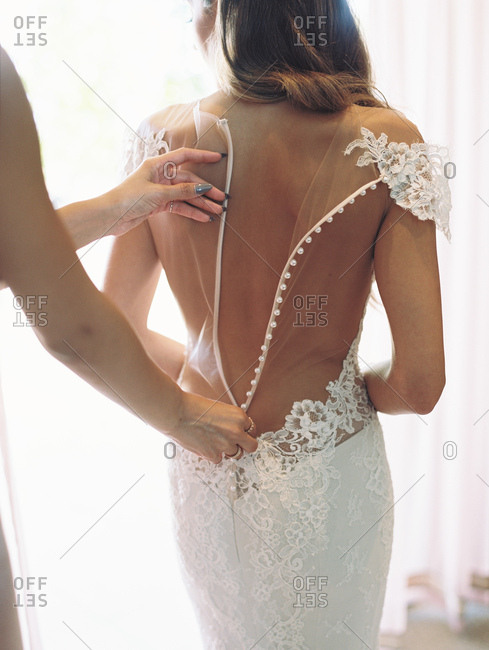 Woman helping bride zip up her dress back