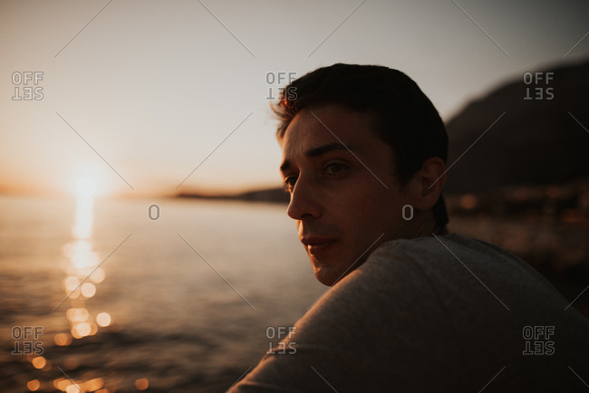 Man sitting on coast of Italy looking out at water