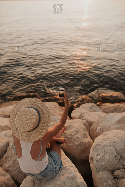 Woman sitting on rocky coast of Croatia taking pictures with phone