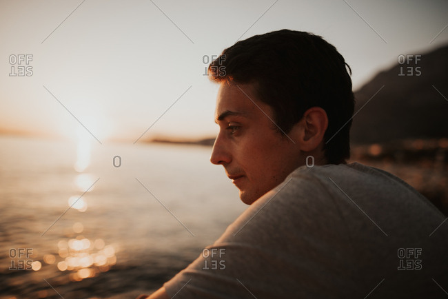 Side view of man sitting on coast of Italy looking out at water