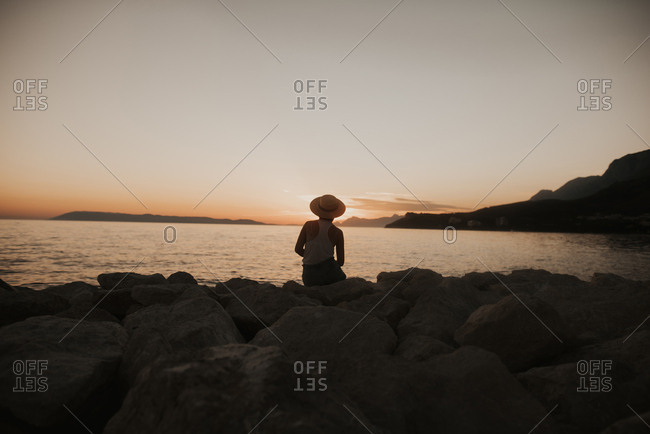 Woman sitting on rocky coast of Croatia at sunset