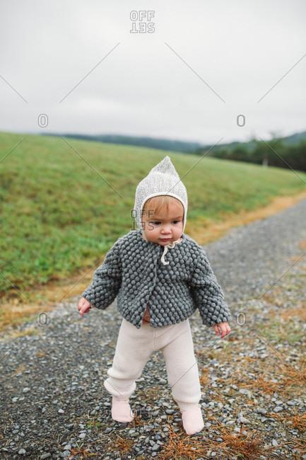 Baby girl wearing bonnet walking on gravel road