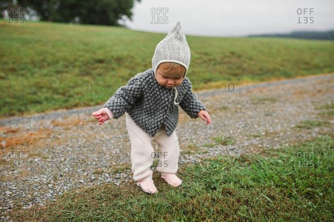 Baby girl wearing bonnet walking beside gravel road