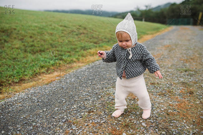 Baby girl wearing bonnet and walking on gravel road