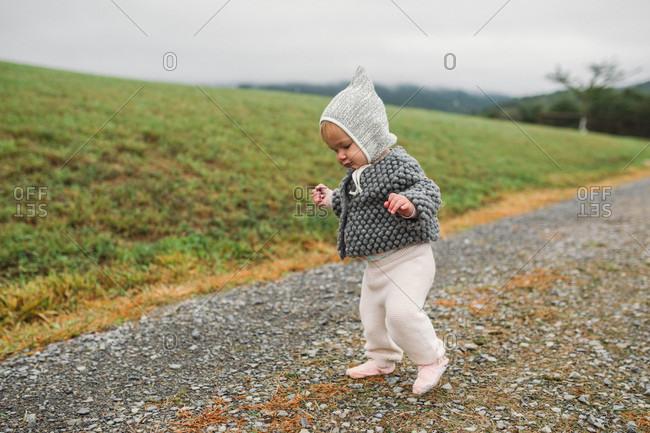 Baby girl wearing bonnet walking on a dirt road