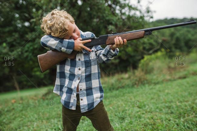 Young boy aiming gun