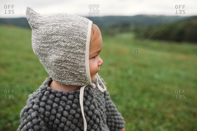 Baby girl wearing bonnet standing in field