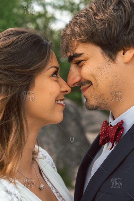Crop side view of cheerful tender man and woman touching with noses and looking at each other with love in wedding day