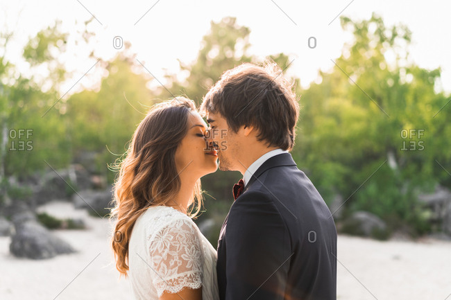 couple in wedding gowns standing on rock and embracing happily against green trees and blue sky